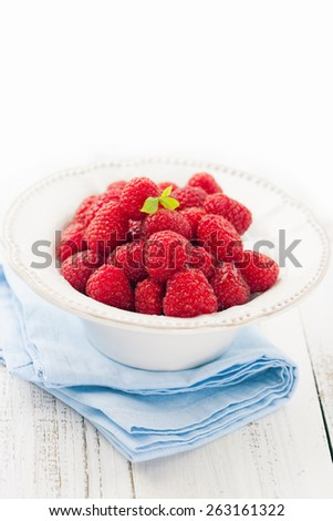Juicy fresh raspberries in a bowl on a white wooden background, selective focus - stock photo