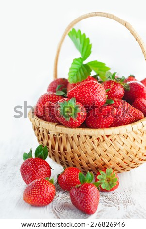 Juicy fresh strawberries in a basket on white wooden background, selective focus - stock photo