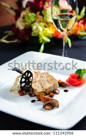 Juicy goose liver on a plate and glass of white wine - stock photo