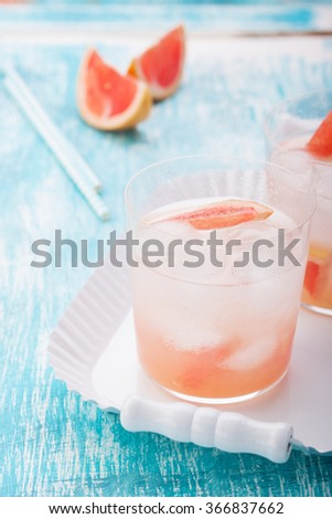 Juicy grapefruit cocktail with ice and alcohol, selective focus  - stock photo