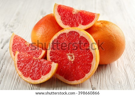 Juicy grapefruits on wooden background - stock photo