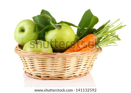 Juicy green apples and carrots with leaves in basket, isolated on white - stock photo