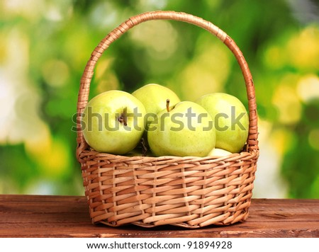 juicy green apples in basket on wooden table on green background - stock photo