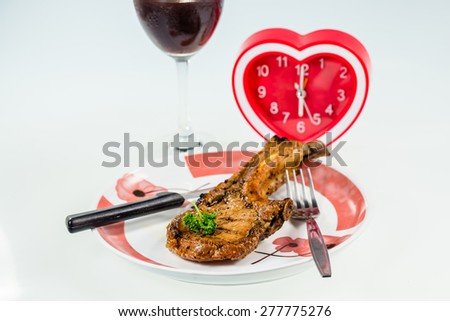 juicy grilled pork chop,Drink Wine for dinner time with heart Clock - stock photo