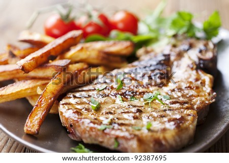 juicy grilled pork chop (neck cut) with greens - stock photo