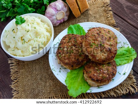 Juicy homecutlets (beef, pork, chicken) and mashed potatoes on a wooden background. - stock photo