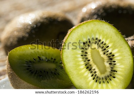 juicy kiwi halves and slices on a plate - stock photo