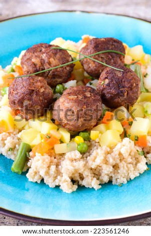 Juicy meatballs and couscous with vegetables,selective focus  - stock photo