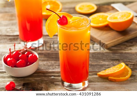 Juicy Orange and Red Tequila Sunrise with a Cherry - stock photo