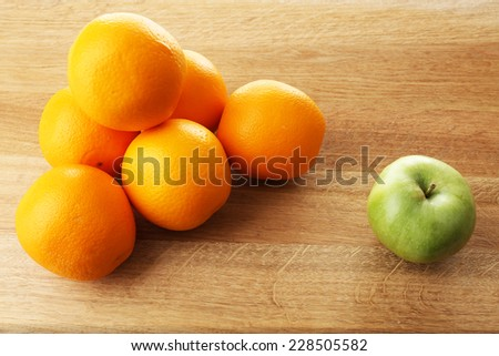 Juicy oranges and green apple on wooden table - stock photo