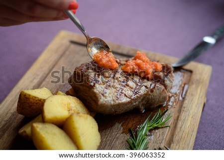 Juicy piece of beef steak with potato on a wooden board with knife and small spoon - stock photo