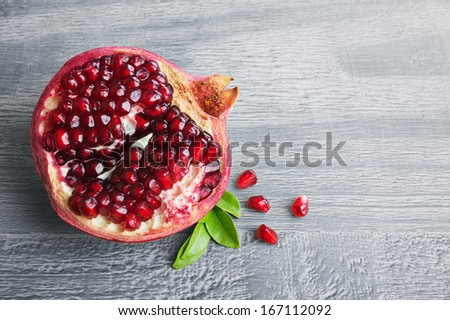 Juicy pomegranate fruit over wooden vintage table - stock photo