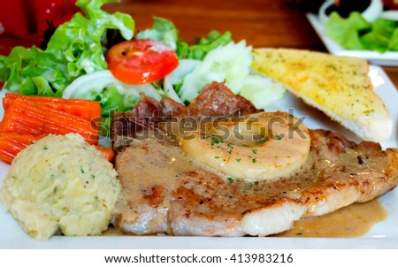 juicy pork chop on white plate with vegetable, pineapple, and mash potato - stock photo