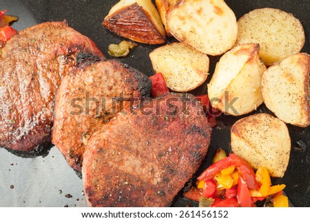 Juicy portions of grilled fillet steak served with roasted potatoes and peppers on black granite board, top view - stock photo