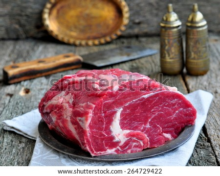 Juicy raw beef steak on wooden table - stock photo