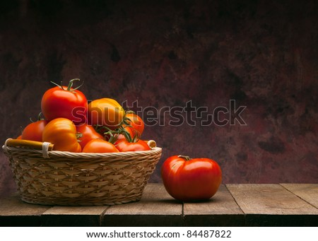 juicy red tomatoes in basket on wooden table - stock photo