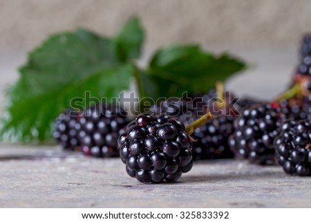 Juicy ripe blackberries close up on an old wooden table - stock photo