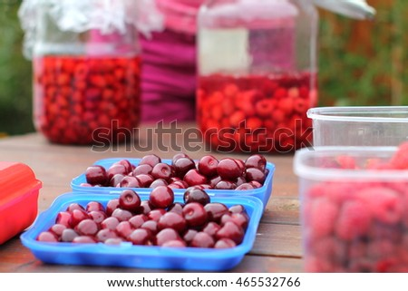 Juicy ripe cherry berries in blue boxes and  two pots with raspberry compote  in background