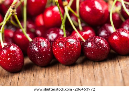 juicy ripe cherry closeup on wooden background - stock photo