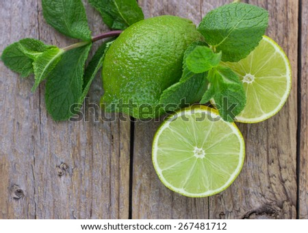 Juicy ripe limes and mint on wooden table - stock photo