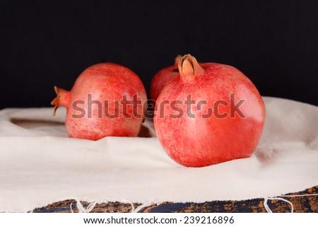 Juicy ripe pomegranates on dark background - stock photo