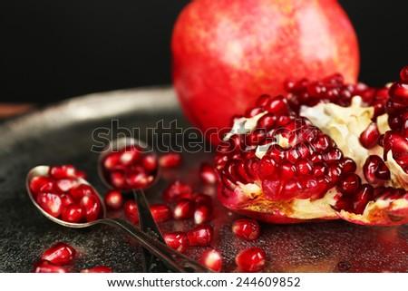 Juicy ripe pomegranates on metal plate, on dark background - stock photo