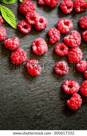 Juicy ripe raspberries with leaves on a dark stone background, top view, selective focus - stock photo