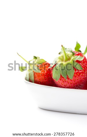 Juicy ripe red whole fresh home grown strawberries in a plain white ceramic bowl with attached green stalks for a healthy finger food snack or cooking and baking ingredient, copyspace on white - stock photo