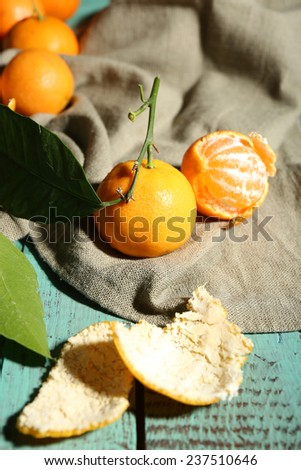 Juicy ripe tangerines with leaves on wooden table  - stock photo
