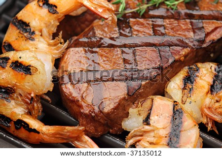 Juicy sirloin steak with grilled shrimps - stock photo