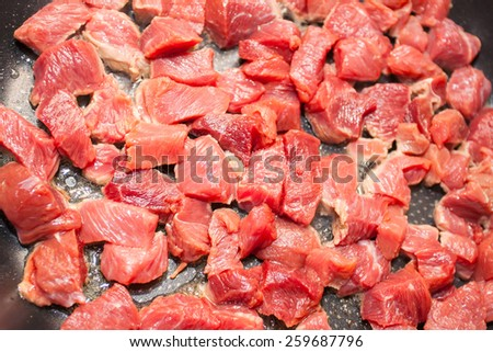 juicy slices of beef in a frying pan - stock photo
