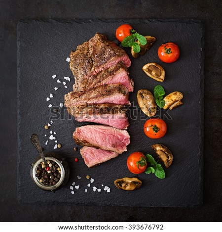 Juicy steak medium rare beef with spices and grilled vegetables. Top view - stock photo