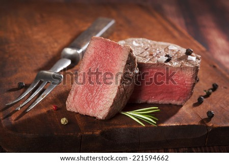Juicy steak on dark wooden background. Luxurious mignon steak, rare. Culinary red meat eating.  - stock photo