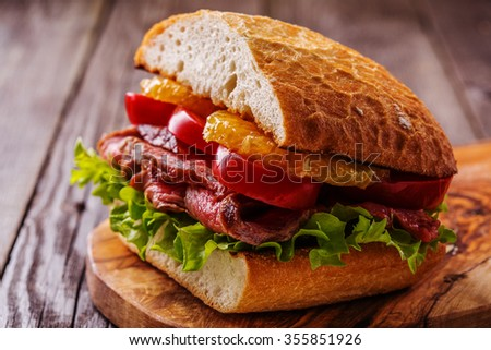 Juicy steak sandwich with vegetables and slices of orange, selective focus. - stock photo