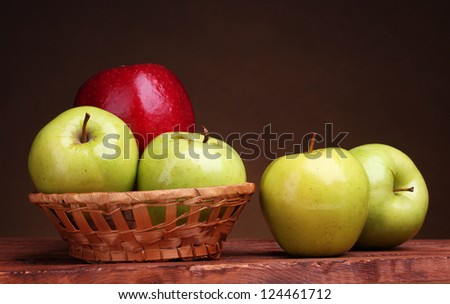 juicy sweet apples in basket on wooden table on brown background - stock photo