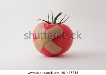 Juicy tomato with a bandage x - stock photo