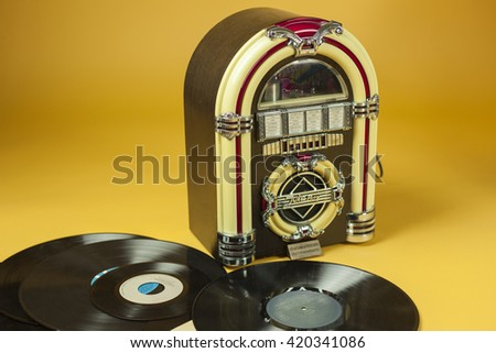 Jukebox and some old vinil records, isolated in yellow background - stock photo