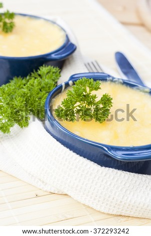 Julienne with mushrooms and cream. Mushroom and cheese gratin in ceramic bowls, on wooden background - stock photo