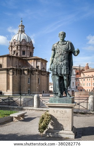 Julius Caesar statue with a wreath at its base and chapel dome and blue sky in the background.  Located near the Roman Forum and Colosseum.  Concepts could include history, leadership, art, others. - stock photo