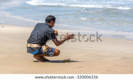July 2015 - A Balinese man praying on Kuta beach, Bali, Indonesia. - stock photo