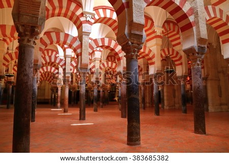 July 12, 2015: Dark interior under countless columns and arches of the Cathedral (Mosque / Mezquita) in Cordoba, Andalusia, Spain