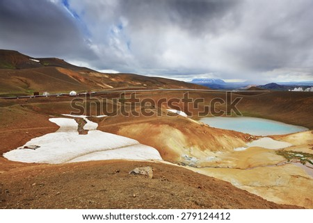 July in Iceland. Krafla lake in the crater of an extinct volcano. On the banks are last year's snow fields - stock photo