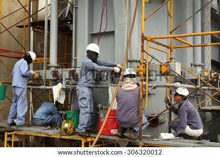 JULY 24, 2015; LAMPANG - THAILAND : Workers are repairing a high voltage transformer station.