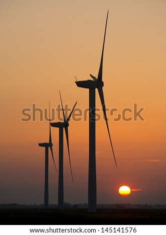 July 2013. Renewable energy. A wind farm on Tick Fen Between Warboys & Chatteris, Cambridgeshire, England seen at sunset. Windmills, blades blot on the landscape .