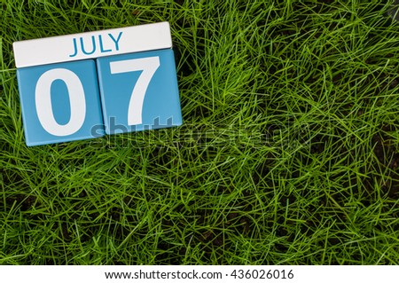 July 7th. Image of july 7 wooden color calendar on greengrass lawn background. Summer day, empty space for text