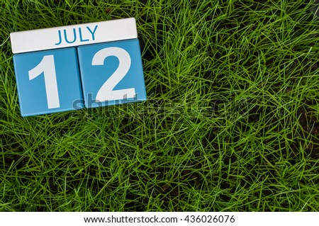 July 12th. Image of july 12 wooden color calendar on greengrass lawn background. Summer day, empty space for text