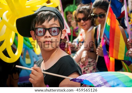 July 3, 2011, Toronto, ON, Canada. Teen male marching in the Toronto Pride Parade wearing sunglasses with Canadian flags. Holding a colorful rainbow flag. Supporting marriage equality and LGBT rights. - stock photo