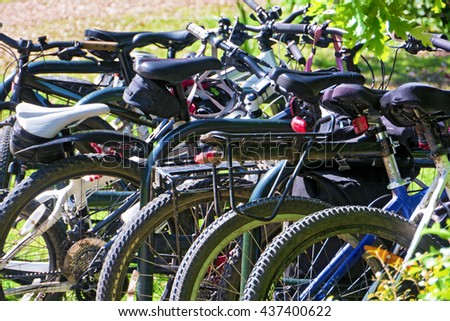 Jumble of parked bicycles; background of bikes -- off-road, scrambler, trail etc -- in leafy setting  - stock photo