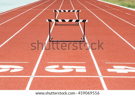 Jump hurdle on running track - stock photo