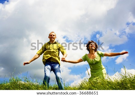 Jump of happiness people on blue sky and green grass background - stock photo